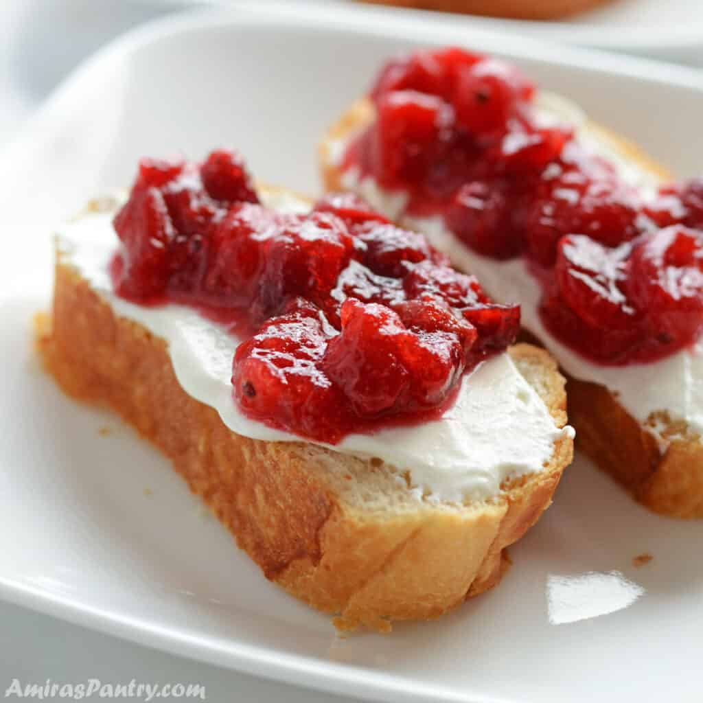Cranberry sauce spread over toast and placed on a white plate.