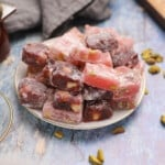 Pink and red Turkish delight squares on a white plate placed on a wooden countertop.