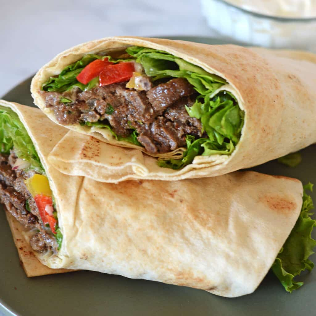 two halves of a beef shawarma wraps stacked on a green plate.