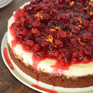 cranberry orange cheese cake on a white plate and placed on a wooden table.