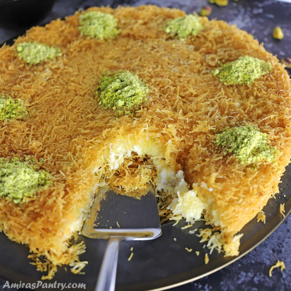 Knafeh garnished with crushed pistachios on a black metal platter..