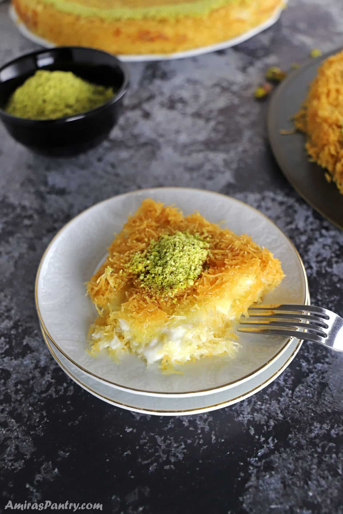 A piece of Kunafa on a white dessert plate with two kunafa platters on the back.