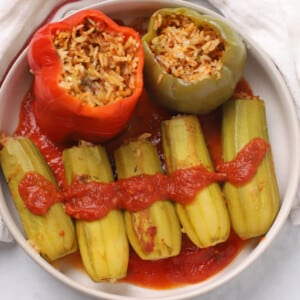 A serving plate with stuffed zucchini and bell peppers with tomato sauce.