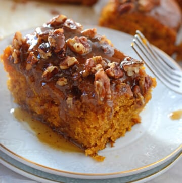 A piece of pecan pumpkin cake on a white dessert plate with a fork next to it.