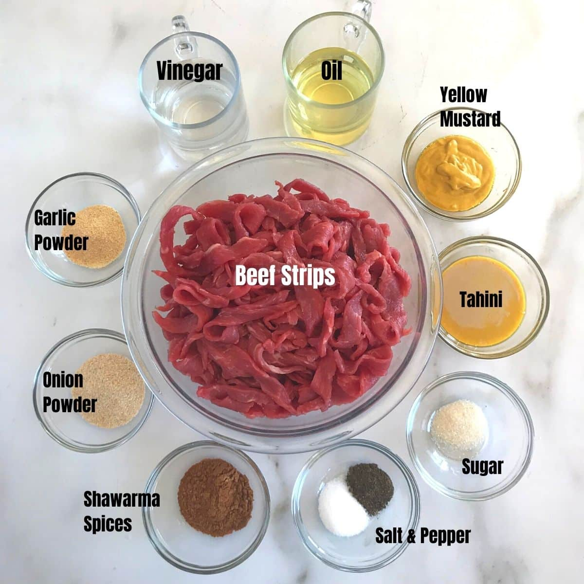 Ingredients for beef shawarma placed on a a white marble table.