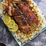 A whole duck placed on a serving platter over a bed or rice garnished with roasted nuts.