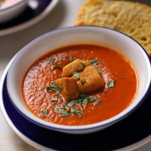A bowl of tomato basil soup with some croutons on the top.