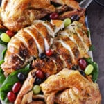 Platter of carved juicy roast turkey decorated with fruits and greens.