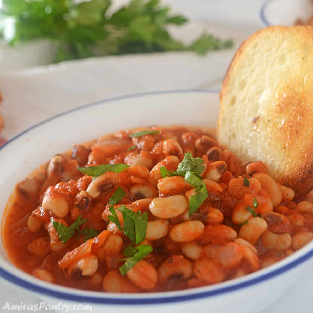 Black eyed peas stew in a white bowl with a dark blue rim. A piece of bread is in the bowl.