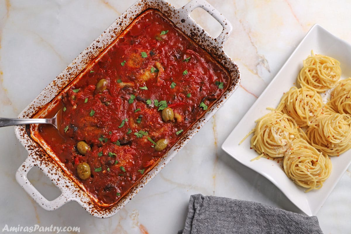 Chicken Cacciatore in a white baking dish with another serving dish of pasta next to it.