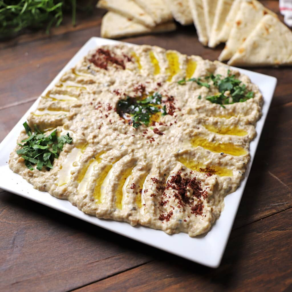 Mutabal dip in a white square plate garnished with sumac and chopped parsley.