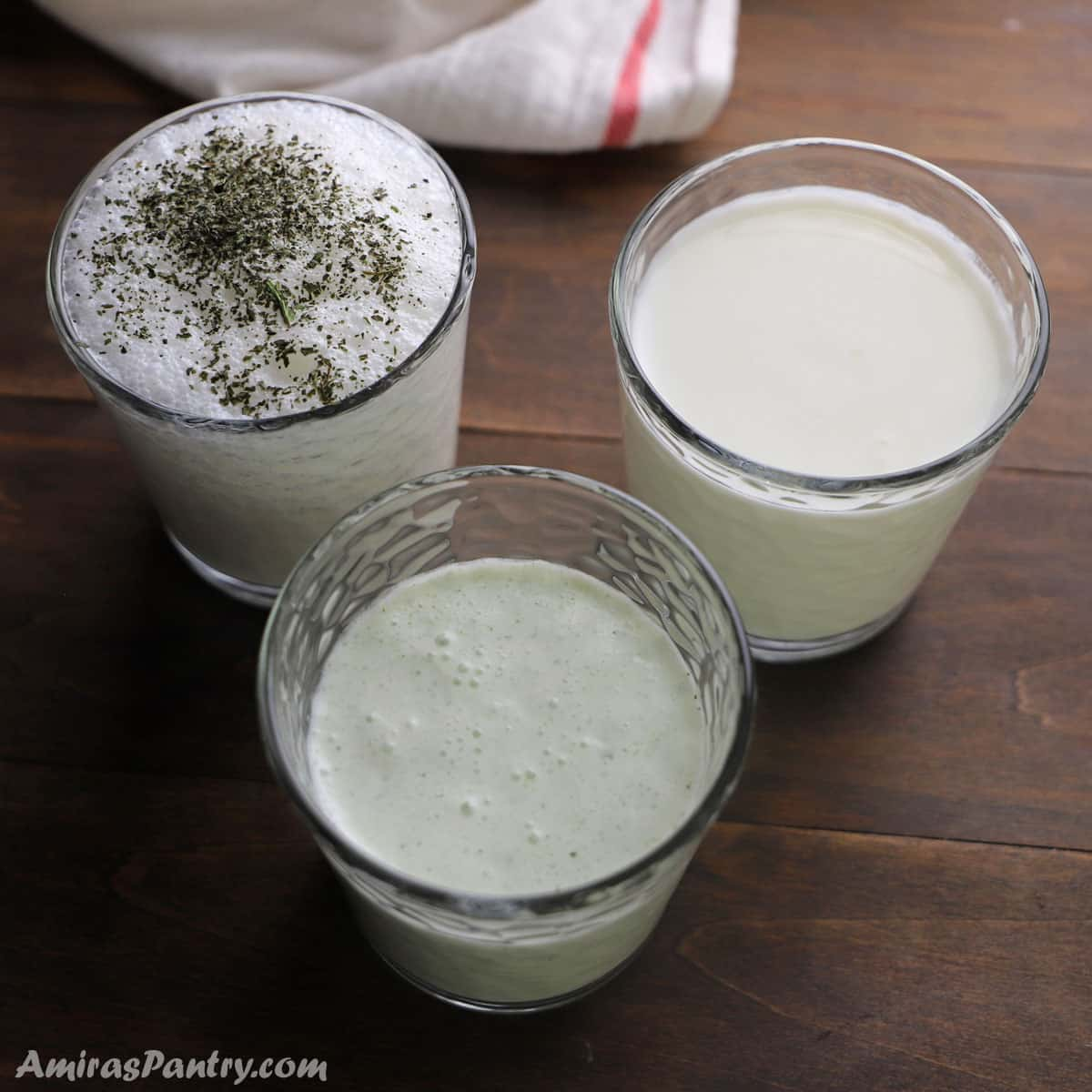 3 cups of different flavors of Ayran placed on a wooden surface.