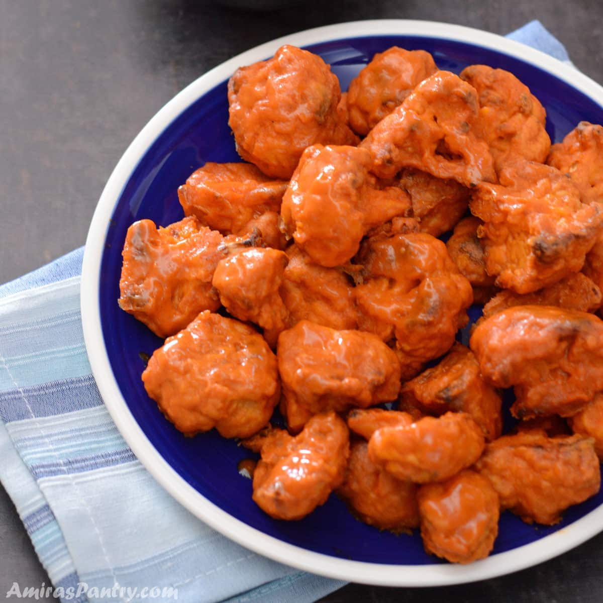 Cauliflower bites on a blue plate with a white rim placed on a black surface.
