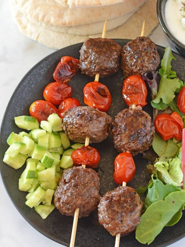 Kofta skewers in a black plate with some greens.