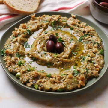 Melitzanosalata served on a green platter garnished with parsley chopped walnuts and kalamata olives.