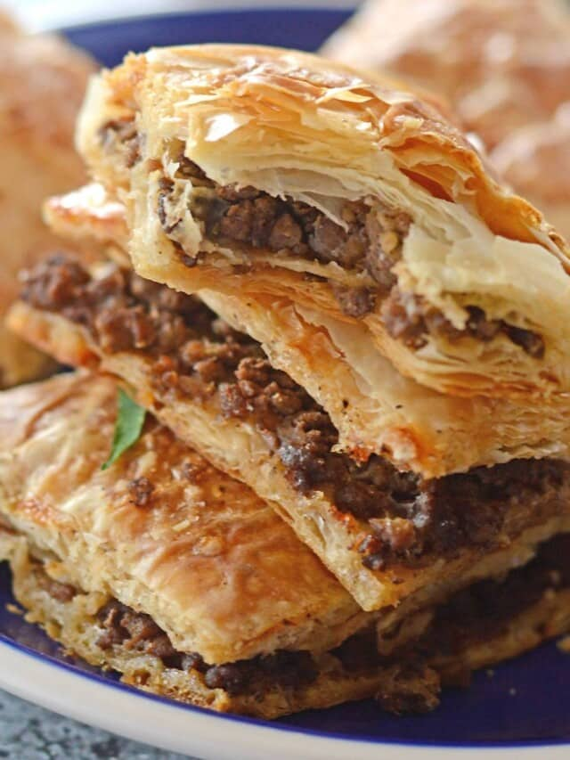 Phyllo meat pie squares stacked on top of each other on a blue plate.