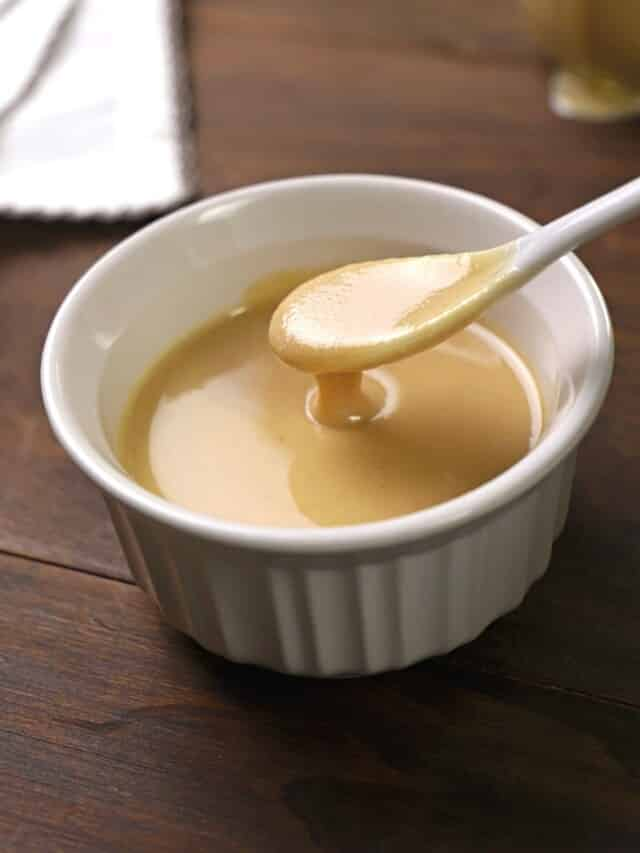 A white spoon scooping some tahini paste out of a white bowl.