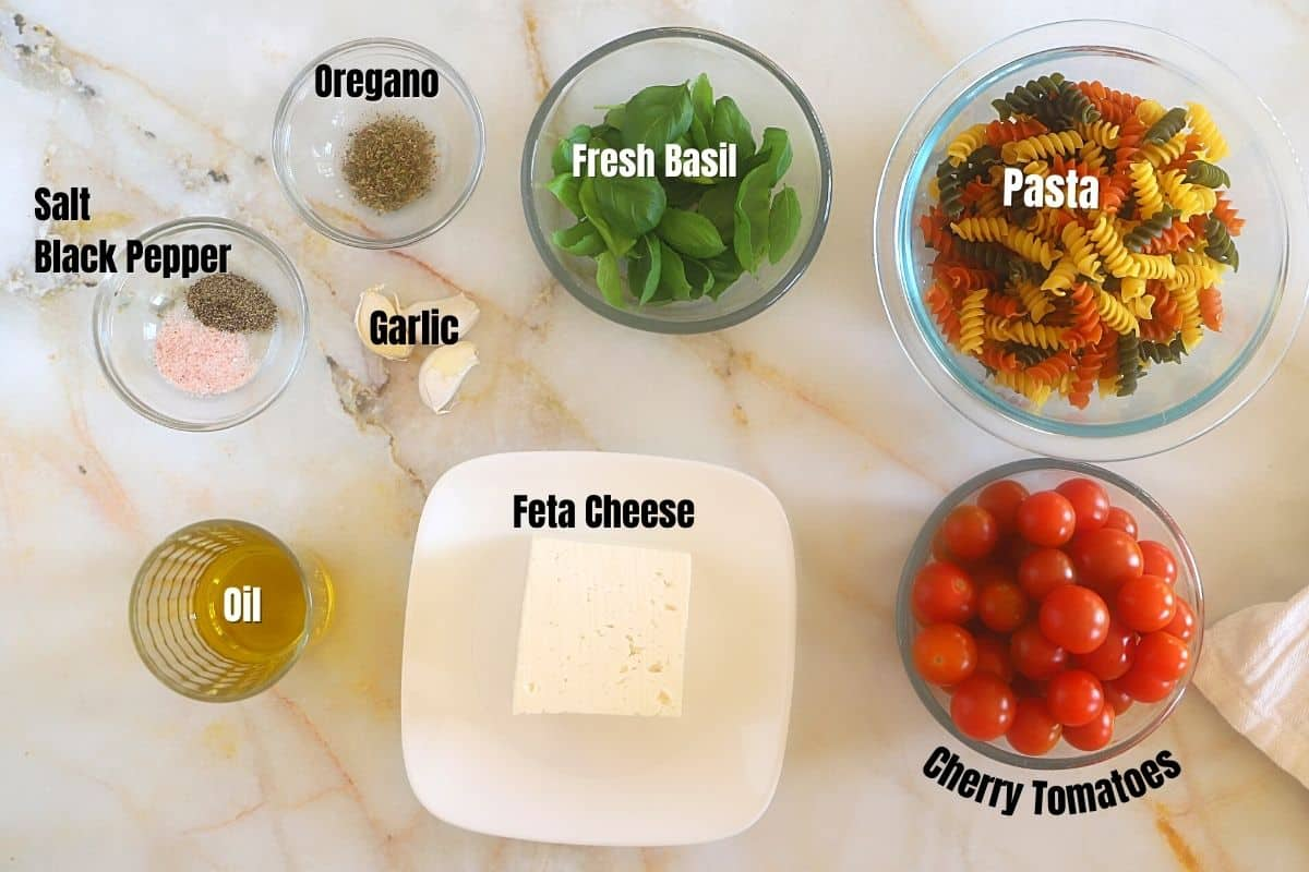 Baked feta pasta ingredients on a marble surface.