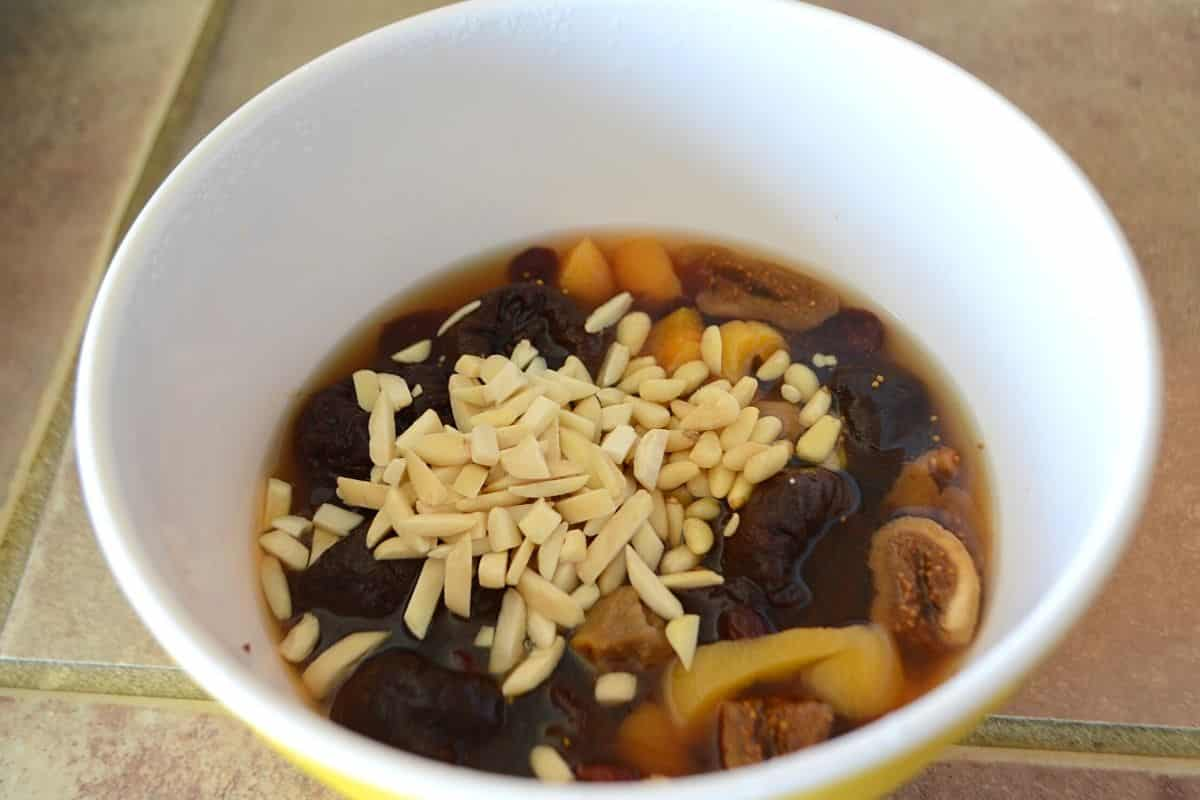 Dried fruits soaked in flavored water with nuts in a deep bowl.