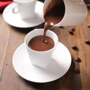 A white carafe pouring hot chocolate into a white mug and all placed on a wooden surface.