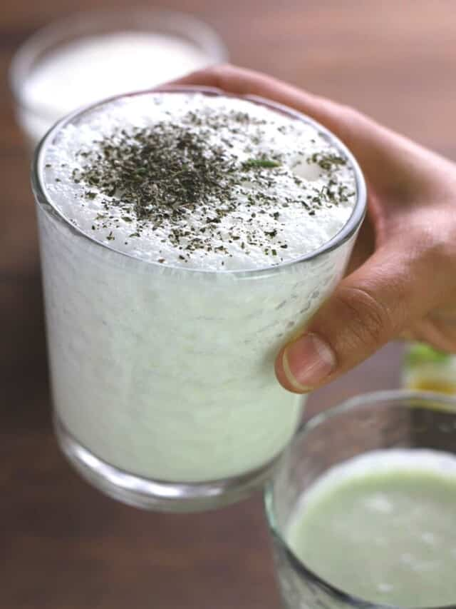A hand holding a cup of Ayran sprinkled with dry mint leaves.