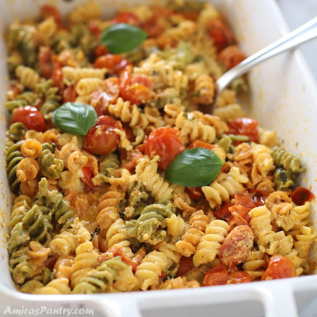 Feta pasta in a white casserole dish with a spoon in it.