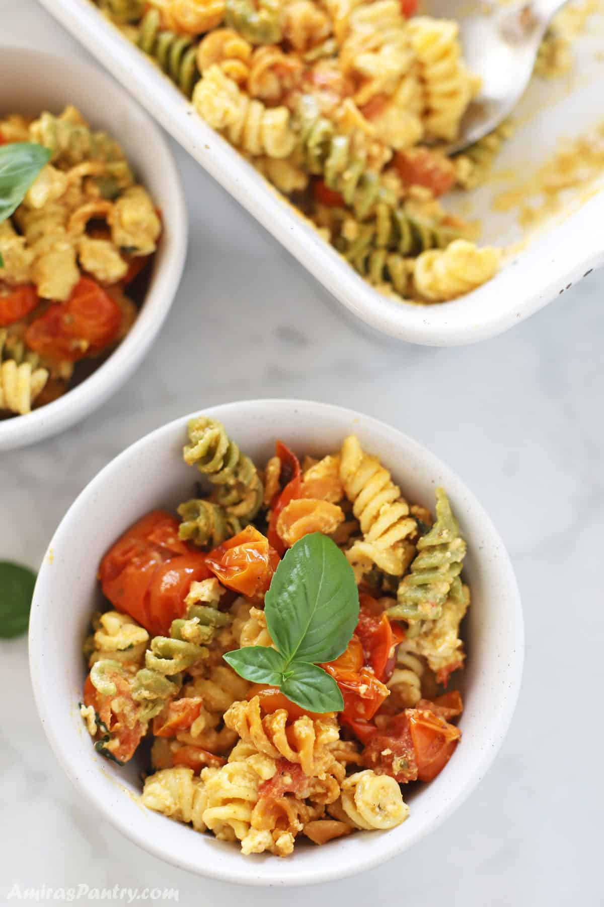 baked feta pasta in a white bowl garnished with fresh basil.
