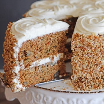 Carrot cake on a cake plate with a piece pulled out of it.