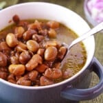 A bowl of ful with a spoon scooping some of the beans out.