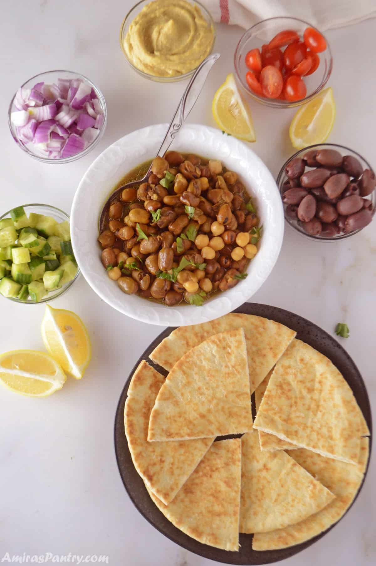 A breakfast table with bowls of ful Medames, hummus, diced onions, tomatoes, cucumber, lemon wedges and pita bread.