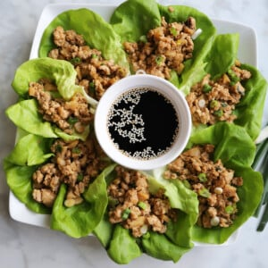 A serving platter filled with chicken lettuce wraps and a sauce bowl in the middle.