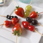 Strawberries Tanghulu Skewers on a white plate with grapes and blue berries tanugul as well.