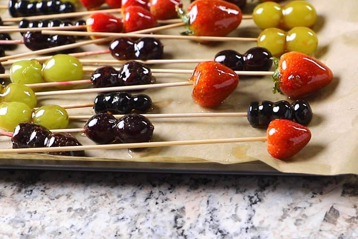Tanghulu candied fruits on skewers and placed on a baking sheet lined with parchment paper.
