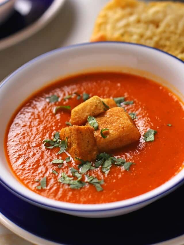 Tomato soup in a white bowl with a blue rim garnished with chopped basil.