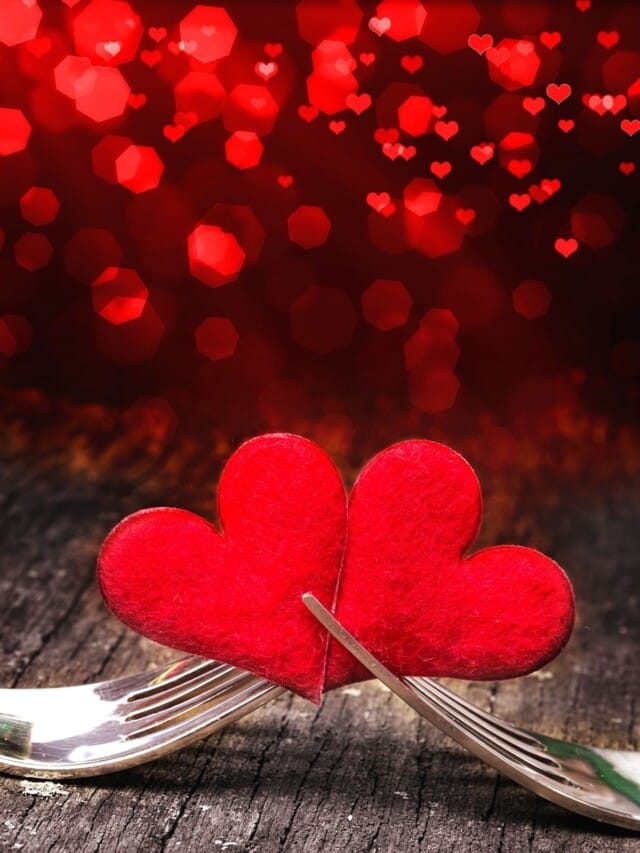 Two hearts placed in two forks with red lights in the back.