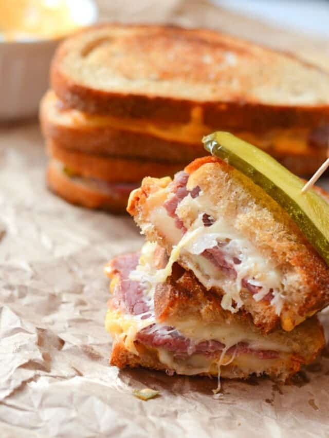 Reuben sandwich cut in half and placed on a crumpled piece of parchment paper.