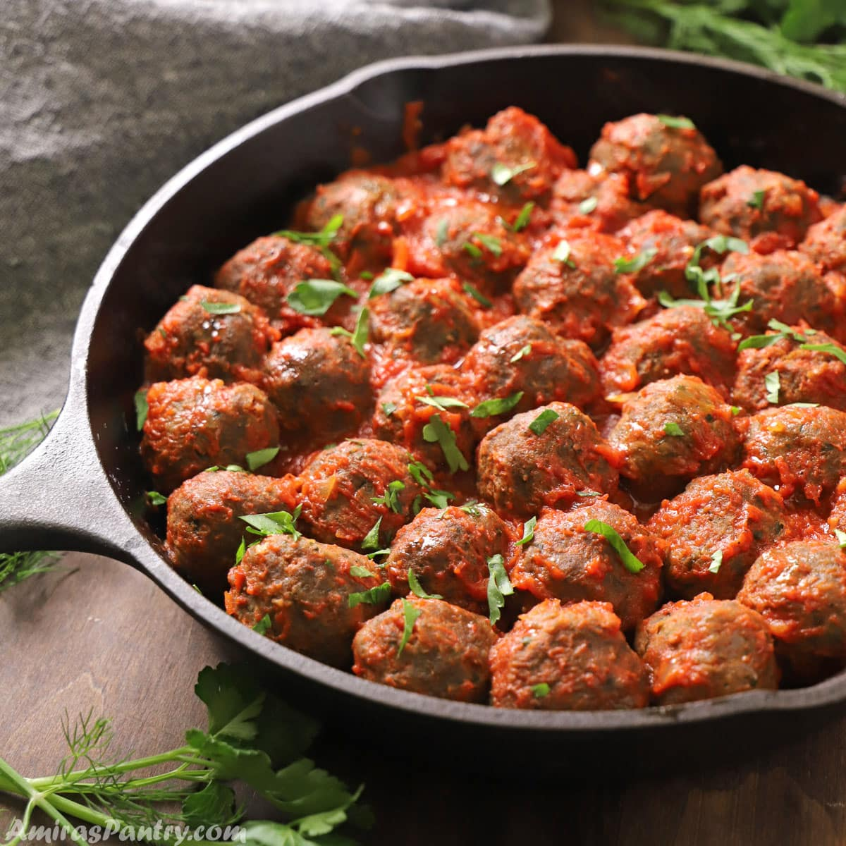 meatballs in a cast iron skillet with tomato sauce and garnished with parsley.