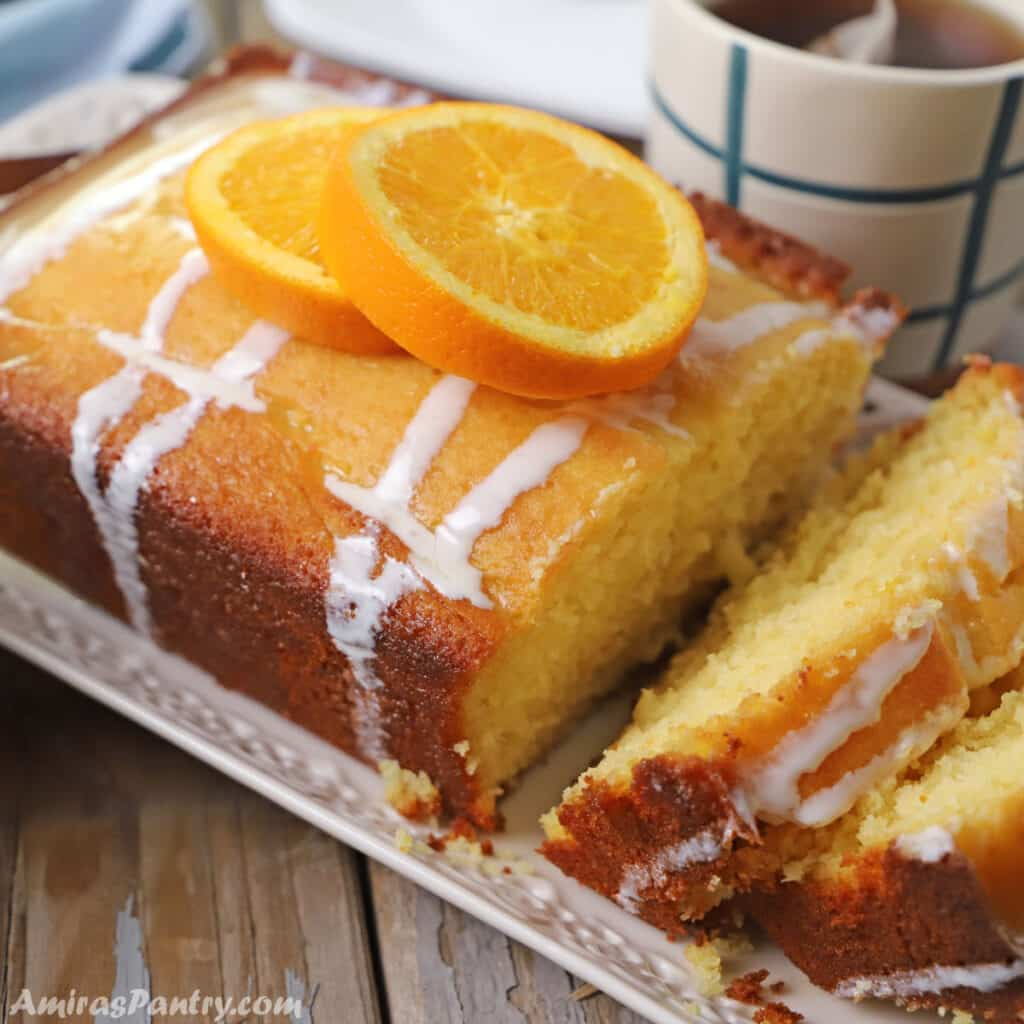 An orange cake slices and placed on a white platter with orange slices on top.