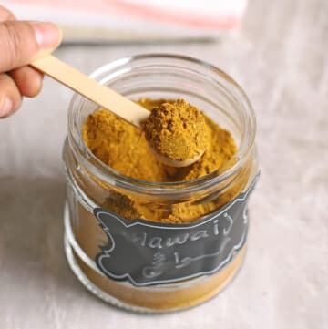 A hand holding a small wooden spoon over a jar of Hawayej mix.