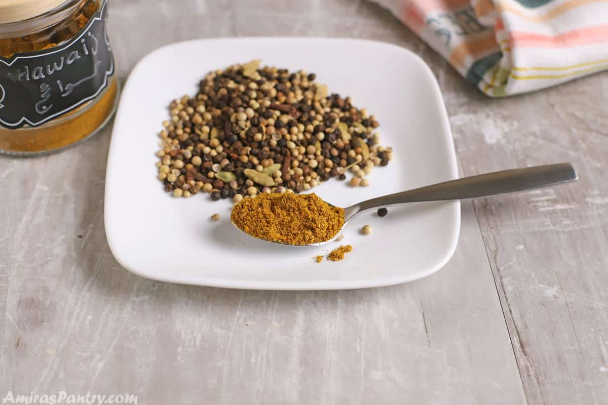 A spoon of Hawayej spice on a white plate with some roasted spices whole spices on the plate.