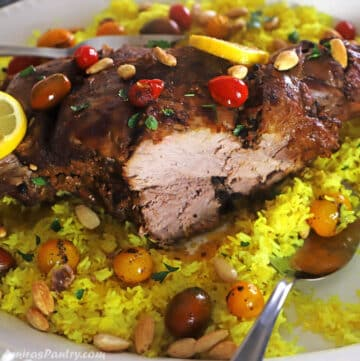 A close look at a leg of lamb with a piece carved out on a yellow rice platter.