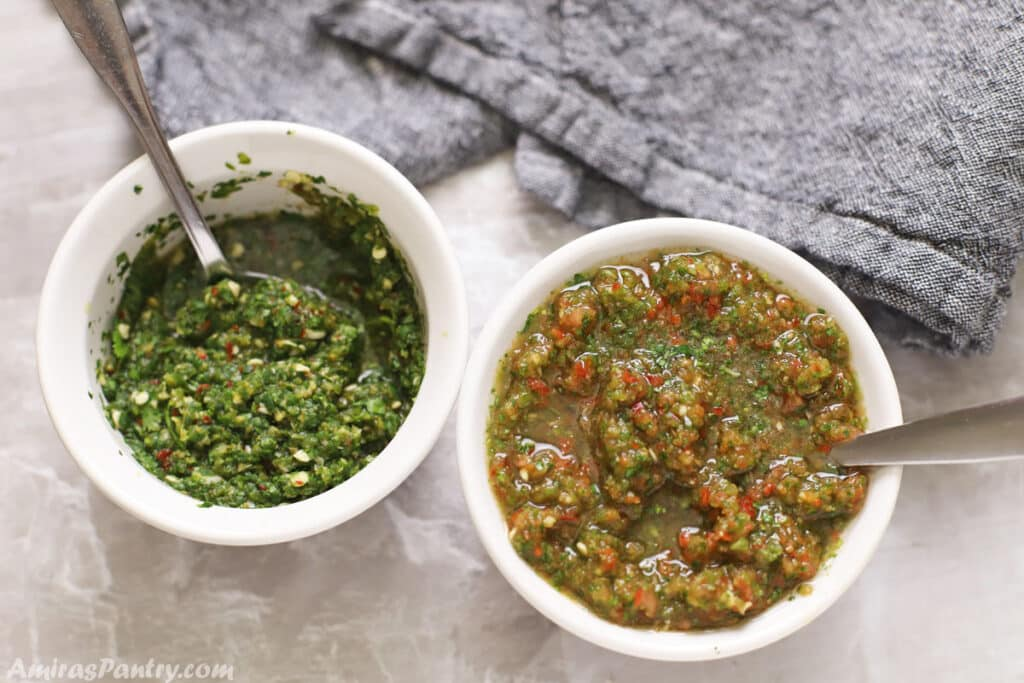 Two bowls of green and red zhoug pesto.