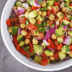Overhead view of a white bowl of chickpea salad.
