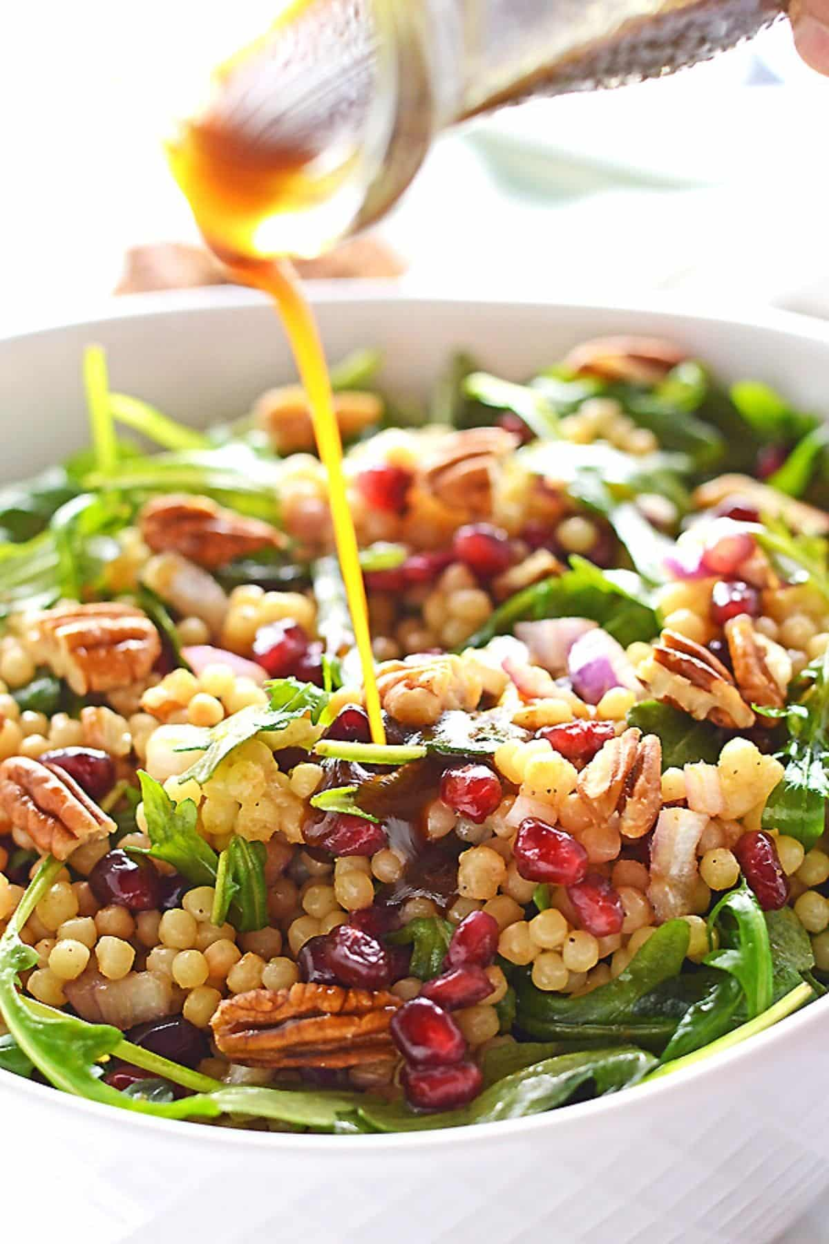 Pearl couscous salad in a deep white bowl with vinegrette pouring over it.