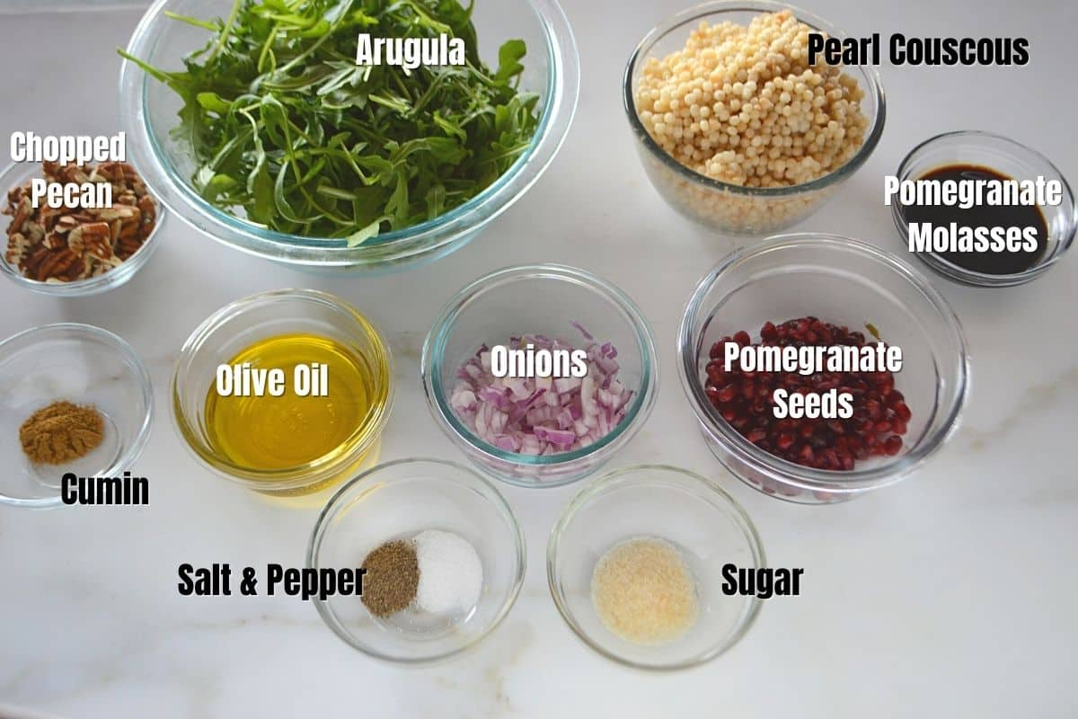 Couscous salad ingredients placed on a white table.