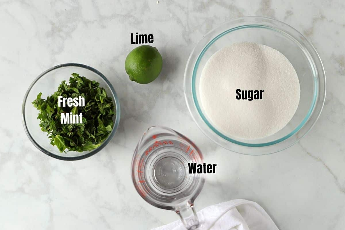 Mint syrup ingredients placed on a white marble table.