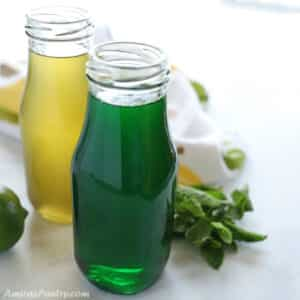 Two bottles of mint syrup one is colored green and the other one without the color placed on a white surface with mint leaves on the side.