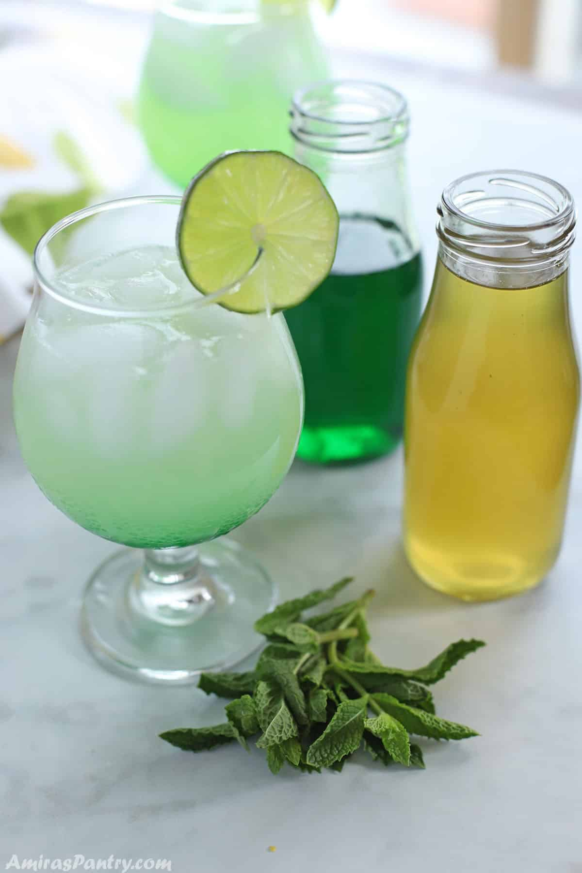 A glass of cold lemonade with green mint syrup at the bottom waiting to be stirred in.