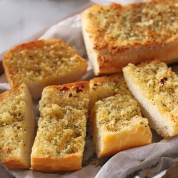 A close up image of garlic bread placed on parchment paper.