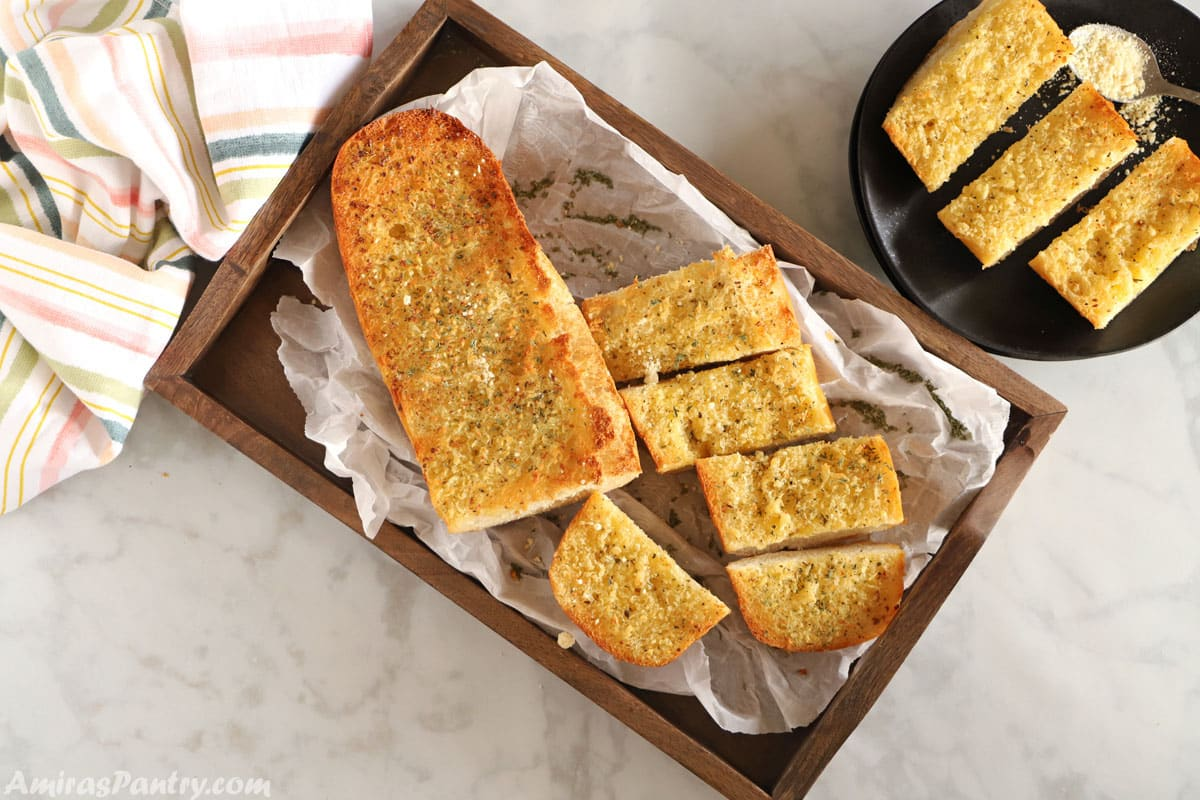 A top view image of garlic bread placed on a wooden tray with a plate of sliced garlic bread on the side.